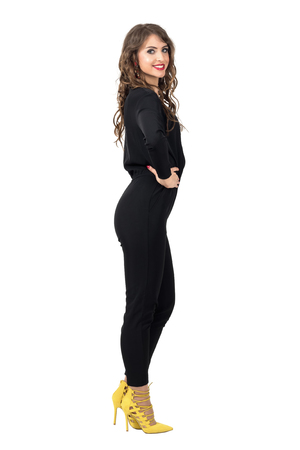 jumpsuit: Side view of beautiful brunette with hands on hips smiling at camera wearing black jumpsuit. Full body length portrait isolated over white studio background. Stock Photo