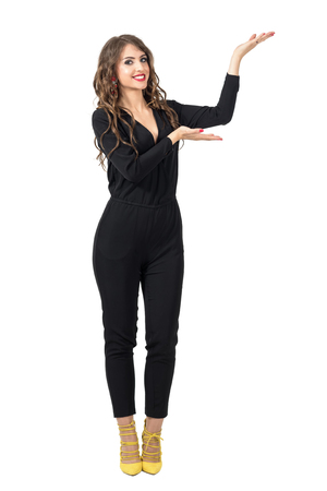 Beautiful fashion model presenter showing hand on copyspace with open palms. Full body length portrait isolated over white studio background.