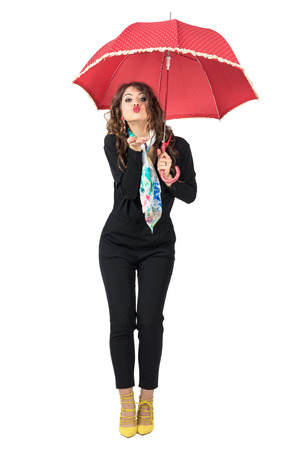 sexy kiss: Gorgeous beauty with scarf and umbrella in black jumpsuit blowing air kiss. Full body length portrait isolated over white studio background. Stock Photo