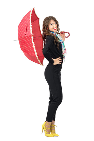 jumpsuit: Side view of beauty fashion woman in black jumpsuit posing with red umbrella. Full body length portrait isolated over white studio background. Stock Photo