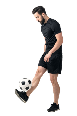 futsal: Side view of freestyle soccer or futsal player juggling ball with his legs. Full body length portrait isolated over white background. Stock Photo