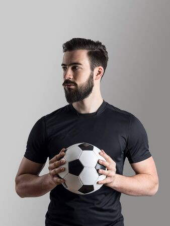 shadowy: Intense shadowy portrait of soccer player holding ball looking away over gray studio background. Stock Photo