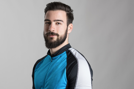 beard man: Portrait of bearded cyclist wearing jersey with copyspace looking at camera over gray studio background