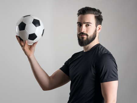 intense: Side view of intense shadow portrait of soccer player holding ball looking at camera.