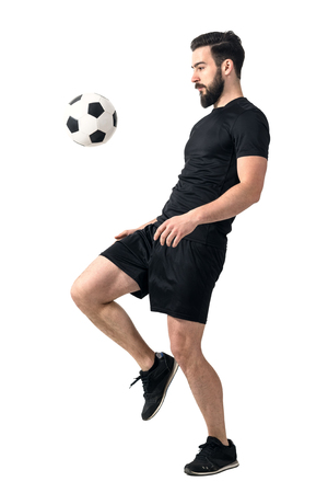 Side view of football or futsal player juggling ball with his knee. Full body length portrait isolated over white background.