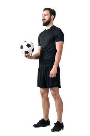one hand: Football or soccer futsal player holding ball in one hand looking up. Full body length portrait isolated over white background.