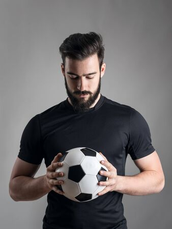 futsal: Intense portrait of football player holding and looking at the ball focused over gray studio background. Determination concept. Stock Photo