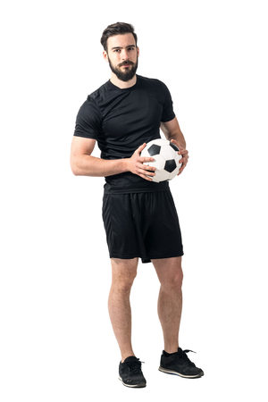 futsal: Confident soccer of futsal player holding ball with daring look at the camera. Full body length portrait isolated over white background.
