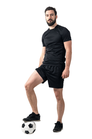provoke: Relaxed serious soccer futsal player standing on the ball looking at camera. Full body length portrait isolated over white background.