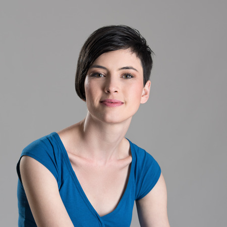 Close up studio portrait of smiling young short haired brunette woman looking at camera over gray background