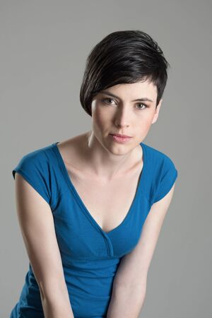 brown eyes: Intense studio portrait of young short hair beauty woman leaning towards and looking at camera over gray background Stock Photo