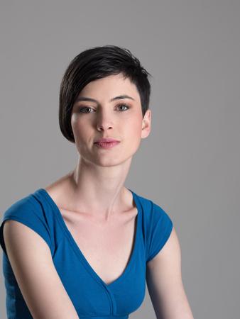 Studio portret van korte haar brunette schoonheid kijken naar camera over grijze achtergrond