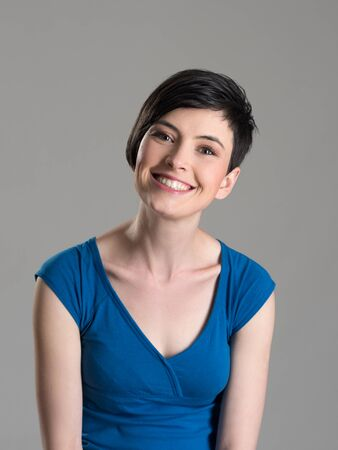 head tilted: Studio portrait of cute lovely short hair brunette beauty smiling at camera with slightly tilted head over gray background Stock Photo