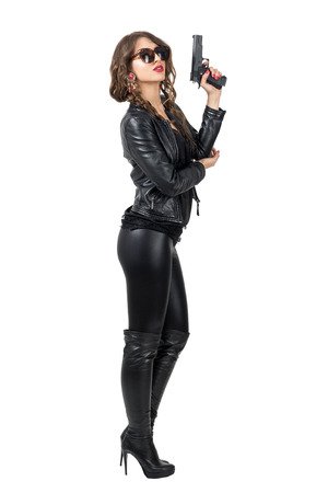 Side view of dangerous woman in leather outfit holding gun with head tilted back. Full body length portrait isolated over white studio background. Stock Photo