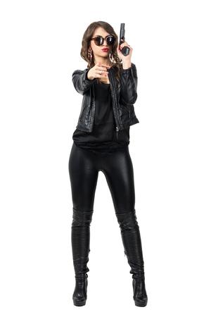 Sexy vrouwelijke politie-vrouw met pistool wijst op camera waarschuwing. Full body lengte portret geïsoleerd op een witte achtergrond studio.