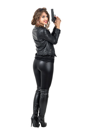 Rear view of dangerous woman holding a gun turn head and smiling at camera. Full body length portrait isolated over white studio background.