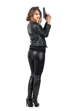 botas: Vista trasera de la mujer peligrosa atractiva que sostiene una cabeza a su vez pistola y sonriendo a la cámara. la longitud del cuerpo Retrato completo aislado sobre fondo blanco del estudio. Foto de archivo
