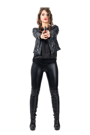 Sexy dangerous woman in black leather boots and jacket pointing handgun at you. Full body length portrait isolated over white studio background. Stock Photo