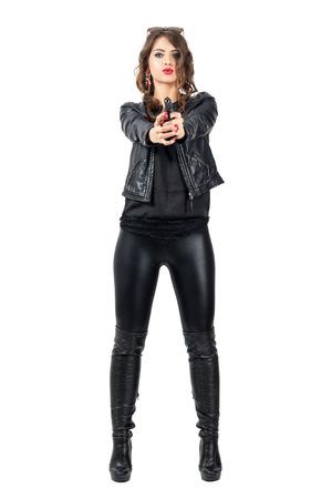 Sexy gefährliche Frau in schwarzem Lederstiefel und Jacke zeigt Pistole auf Sie. Ganzkörper-Länge Portrait über weißem Hintergrund Studio isoliert.