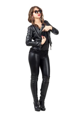 botas: espía hembra atractiva que desgasta la ropa de cuero que tiran de pistola de su chaqueta. la longitud del cuerpo Retrato completo aislado sobre fondo blanco del estudio.