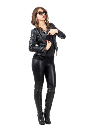 leather: Sexy female spy wearing leather clothes pulling handgun from her jacket. Full body length portrait isolated over white studio background. Stock Photo