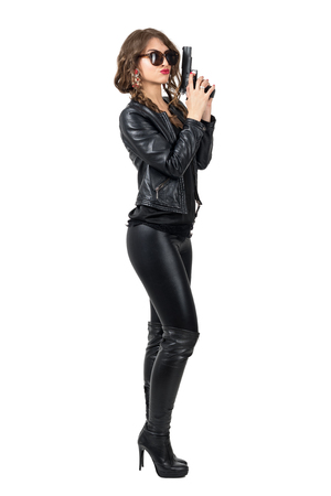 Sexy dangerous woman wearing sunglasses and leather clothes holding a gun with both hands side view. Full body length portrait isolated over white studio background.