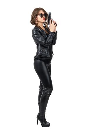 Sexy gevaarlijke vrouw draagt ??een zonnebril en lederen kleding met een pistool met beide handen zijaanzicht. Full body lengte portret geïsoleerd op een witte achtergrond studio. Stockfoto - 56633136