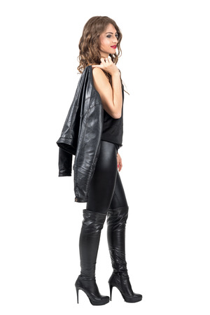 sexy boots: Side view of young beautiful woman with curly hair walking and pensive looking away. Full body length portrait isolated over white studio background.