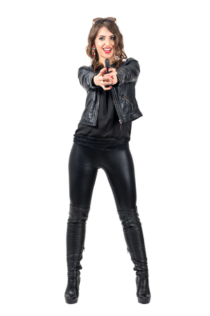 Happy smiling attractive woman in black leather pointing gun at camera. Full body length portrait isolated over white studio background. Stock Photo