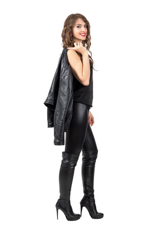 Stylish beautiful woman in leather boots and pants carrying leather jacket over her shoulder. Full body length portrait isolated over white studio background.