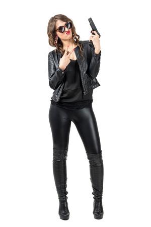 modelos negras: Belleza sexy vestido de cuero negro y botas de la celebración de arma de fuego con dos dedos de la mano de la paz gesto. la longitud del cuerpo Retrato completo aislado sobre fondo blanco del estudio.