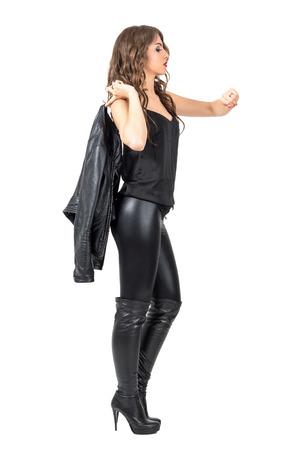 rocker girl: Vista lateral de la elegante belleza morena con botas de cuero que llevaban chaqueta en vez de comprobar el hombro. la longitud del cuerpo Retrato completo aislado sobre fondo blanco del estudio.