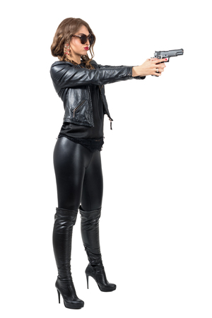Side view of dangerous tough woman in leather clothes shooting a gun. Full body length portrait isolated over white studio background. Stock Photo
