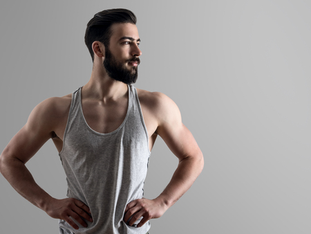 sleeveless top: High contrast portrait of young fit bearded man with hands on hips looking away with copyspace over gray background