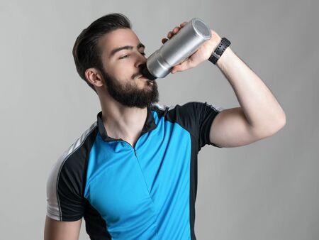 or thirsty: agua potable con barba ciclista joven sedienta de la botella pl�stica