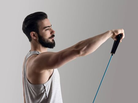 toning: Side view of young athlete in tank top workout with elastic resistance band doing shoulder exercises.