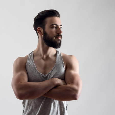 Dramatic portrait of confident strong handsome bearded athlete with crossed arms looking away over gray background