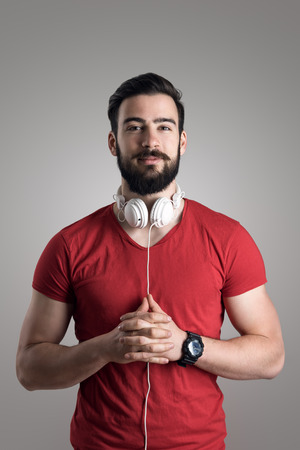 portrait studio: Portrait of young bearded man in red shirt with headphones around his neck Stock Photo
