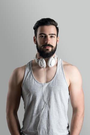healthy looking: Healthy fit young bearded man in singlet with headphones around neck looking at camera.
