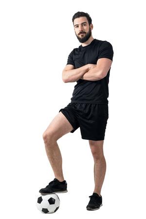 ropa deportiva: jugador de fútbol de pie sobre el balón con una pierna presenta con los brazos cruzados. Retrato de cuerpo completo del cuerpo sobre fondo blanco.