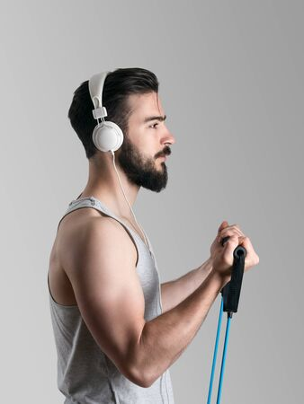elastic band: Side view portrait of young male athlete training biceps muscle with resistance band while listening to music with headphones