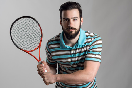 a shirt: Concentrated tennis player in polo shirt holding racket with both hands waiting for service.