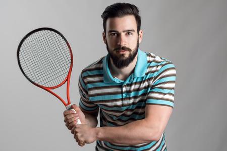 camisas: tenista se concentró en camisa de polo que sostiene la raqueta con las dos manos a la espera de servicio.