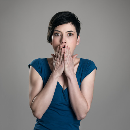 Portrait of shocked frightened short hair pretty woman looking at camera over gray studio background