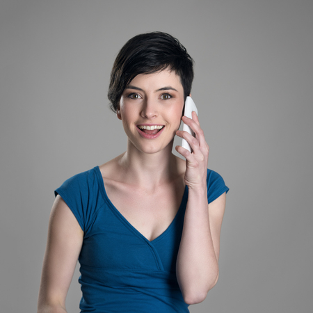 studio model: Smiling friendly short hair woman talking on the cellphone looking at camera over gray studio background. Stock Photo