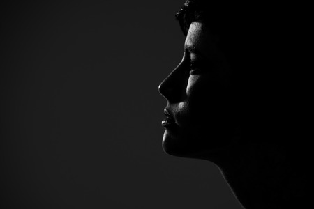 high contrast: Abstract silhouette of young pretty woman looking away. Profile view.