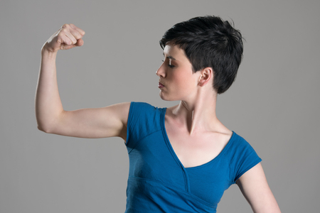 Slim young short hair woman flexing arm bicep muscle over gray studio background.