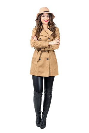girl boots: Happy smiling pretty woman wearing hat and coat with crossed arms looking at camera. Full body length portrait isolated over white studio background.