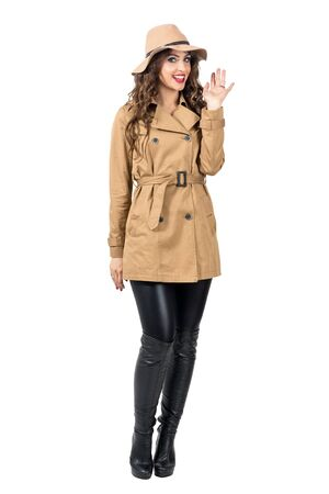 waving: Young pretty woman in coat and hat waving hand and greeting at camera. Full body length portrait isolated over white studio background. Stock Photo