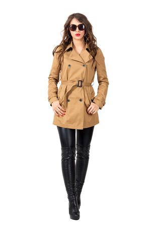 catwalk model: Runway catwalk model in autumn clothes wearing sunglasses walking forward. Full body length portrait isolated over white studio background. Stock Photo